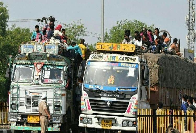 पैदल जा रहे श्रमिकों को ट्रक में सवार कराता पुलिसकर्मी